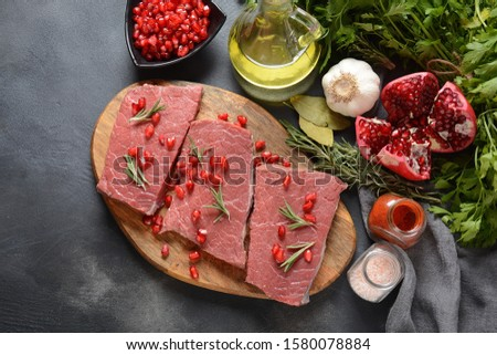 Raw beef with ingredients, herbs, spices and pomegranate. Paleo diet #1580078884