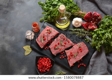 Raw beef with ingredients, herbs, spices and pomegranate. Paleo diet #1580078887