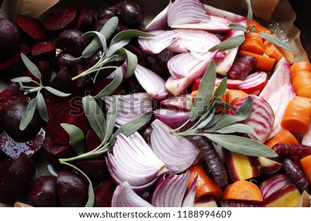 Raw beets of different varieties, carrots and onions prepared for baking in a pan.
