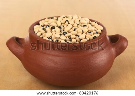 Raw black-eyed peas (cowpeas) in rustic bowl photographed on wood (Selective Focus, Focus on the peas in the front of the bowl)