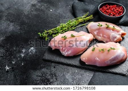 Raw boneless chicken thighs fillet. Black background. Top view. Copy space ストックフォト ©