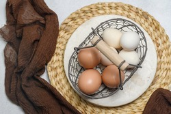 Raw brown and white chicken egg served on old vintage wire tray on the bamboo plate and white table. Top View