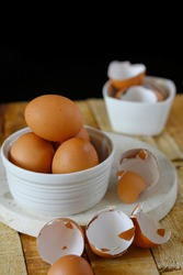 Raw brown chicken egg and peeled eggshell. Served on white bowl on the marble cutting board and wooden table with black background.