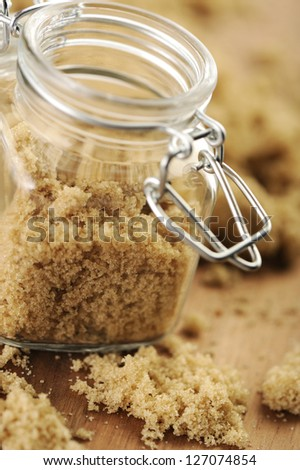 Raw brown sugar in a small jar.
