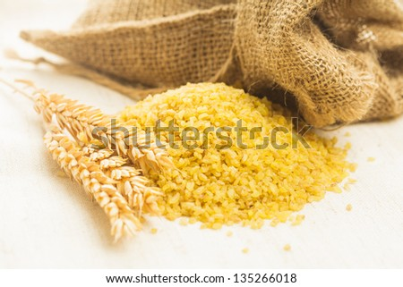 Raw bulgur heap on the linen textile