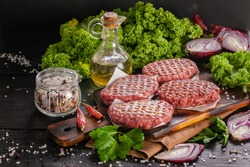 Raw burger cutlets made from organic meat. Food still life on a dark wooden background