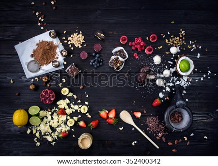 Raw cakes, fresh fruits and nuts for desserts beautifully arranged on a black wooden table/Raw cakes and fresh fruits