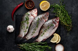 Raw carp with lemon and rosemary on a black plate on a stone background River organic fish