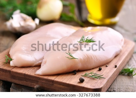 Raw chicken breasts and spices on wooden cutting board, close up view