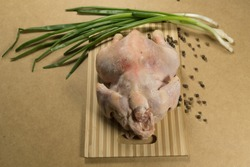 Raw chicken carcass, chicken. Raw chicken carcass with spices and herbs on a cutting board on a wooden table