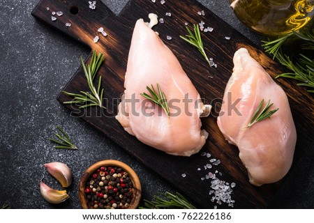 Raw chicken fillet on a cutting board at black background. Preparation for cooking. Top view copy space. Сток-фото ©