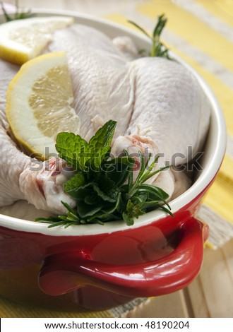 Raw chicken in a red crock pot, stuffed with fresh herbs and lemon, ready for cooking.