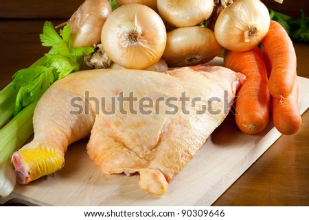Raw chicken leg, onions, carrots and celery over a chopping board