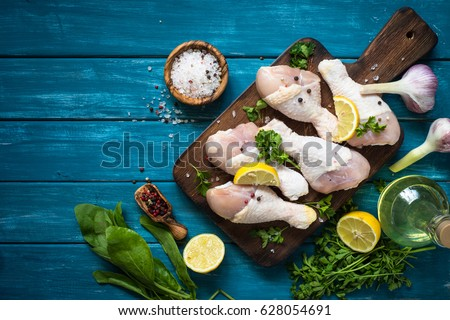 Raw chicken legs with herbs and spices on cutting board. Top view. Food ingredient. #628054691