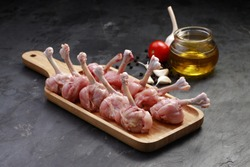 Raw chicken lollipop,ten pieces of chicken lollipop arranged on a serving board with oil, tomato and garlic on background with grey textured base