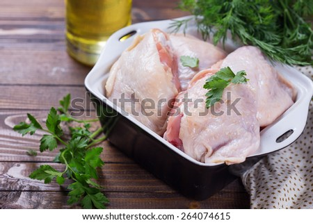 Raw chicken meat in bowl  on dark table. Selective focus. Rustic style.