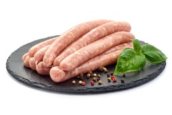 Raw Chicken Sausages on a slate shale plate with spices and basil, close-up, isolated on white background.