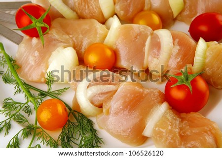 raw chicken shish kebab on white plate