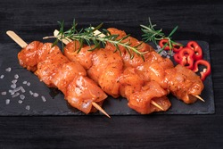 Raw chicken skewers in marinade with spices on a black plate and on a wooden table.Chicken meat close up. Raw marinated and spicy chicken skewers.Top view. Tasting diet meat.