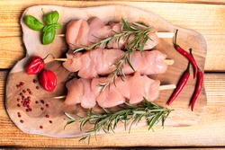 Raw chicken skewers of tender chicken fillet on skewers. Chicken skewers of a kitchen cutting board with a branch of razmarin and hot pepper. Kebab. On a wooden background. Top view.