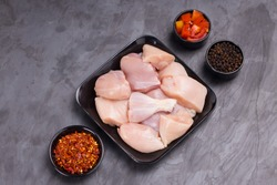 Raw chicken tender curry cut without skin arranged on black plate and garnished with tomato slices, chilli flakes and pepper on stone textured or graphite colour background