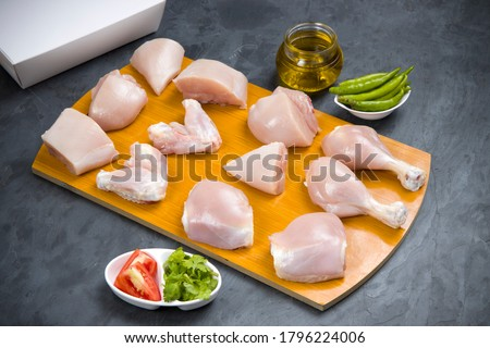 Photo of  Raw chicken tender curry cut without skin arranged on wooden board and garnished with coriander leaf ,tomato slices,fresh green chilli,oil and lemon slices with delivery box on stone textured