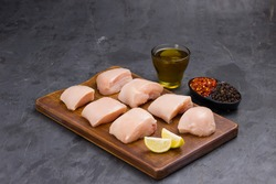 Raw chicken tender fry cut without skin arranged on wooden board and garnished with oil,lemon slices , chilly flakes and black pepper on stone textured or graphite colour background