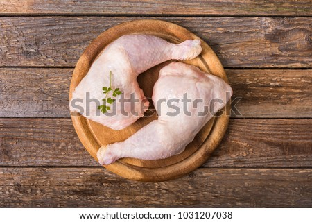Raw chicken thighs on a round wooden cutting board on a wooden background.Top view Foto stock ©