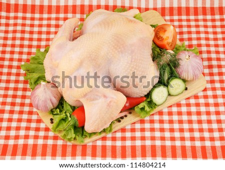 Raw chicken with vegetables on cutting board on tablecloth