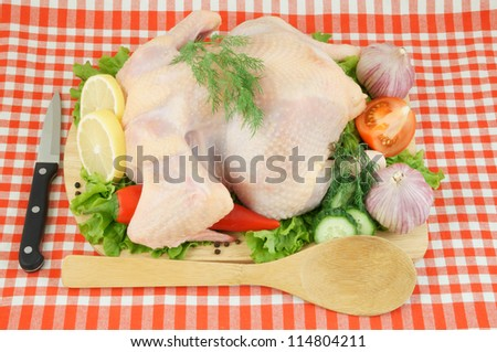 Raw chicken with vegetables on cutting board on tablecloth with knife and spoon