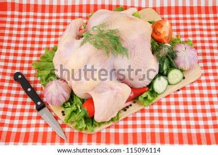 Raw chicken with vegetables on cutting board with knife on tablecloth
