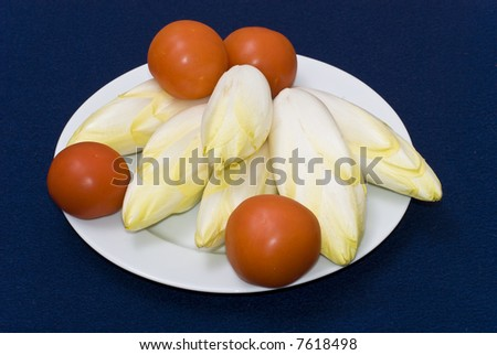 Raw chicory with tomatos on a plate. The first stage of the cooking process.