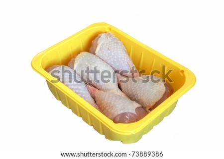 Raw  chiken legs in the box over white background - stock photo