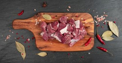 Raw chopped lamb fillet, diced tenderloin or cubed mutton sirloin meat on black stone plate background. Fresh sheep fillet, loin filet with spices on wood board top view