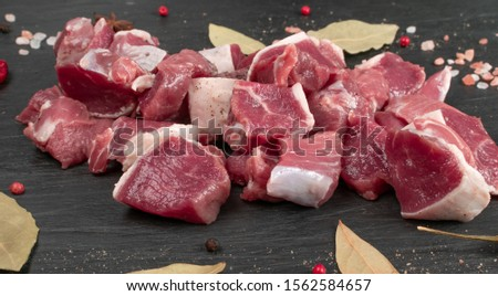 Raw chopped lamb fillet, diced tenderloin or cubed mutton sirloin meat on black stone plate background. Fresh sheep fillet, loin filet with spices closeup