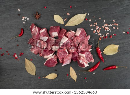 Raw chopped lamb fillet, diced tenderloin or cubed mutton sirloin meat on black stone plate background. Fresh sheep fillet, loin filet with spices top view