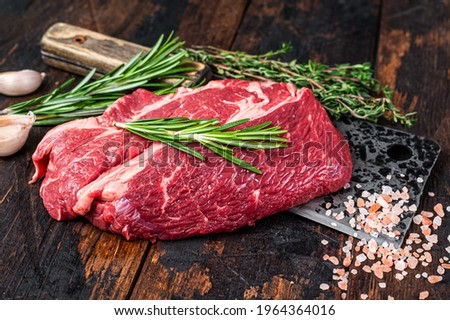 Raw Chuck eye roll Black Angus prime beef steak on butcher cleaver. Dark wooden background. Top view Stock photo ©