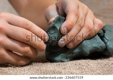 Raw clay in the hands of child