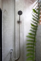 Raw concrete wall with Shower head on a bathroom