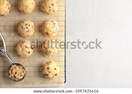 Raw cookie dough with chocolate chips and scoop on parchment paper, top view Stock photo ©