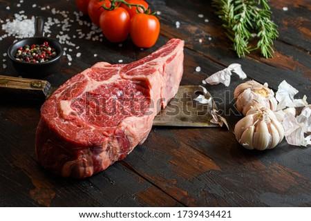 Raw Cowboy steak on dark wooden vintage table background. Ribeye Steak, Bone-In steak or tomahawk steak BBQ with seasonings, rosemary, tomato, chikie, garlic, peppercorn, salt with meat cleaver knife