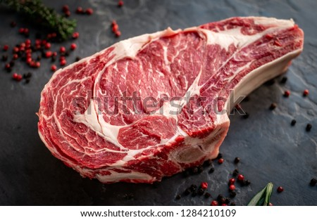 raw cowboy steak with seasonings on stone background, prime rib eye on bone