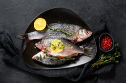 Raw crucian carp with lemon and thyme on a black plate. River organic fish. Black background. Top view