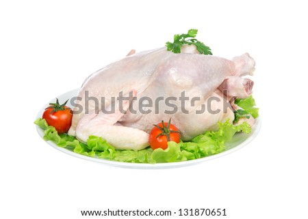 Raw crude chicken on a plate garnished with vegetables salad, tomatoes and greens isolated on a white background