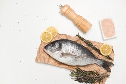 Raw dorada fish or gilt-head bream on paper over white background, flat lay, top view