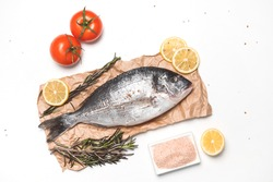 Raw dorada fish or gilt-head bream over white background, flat lay, top view