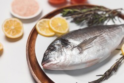 Raw dorado fish or gilt-head bream served on white plate on white background, flat lay, top view