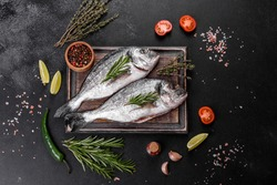 Raw dorado fish with spices cooking on cutting board. Fresh fish dorado. Dorado and ingredients for cooking on a table