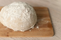 Raw dough covered with flour on a wooden cutting board food photography recipe idea
