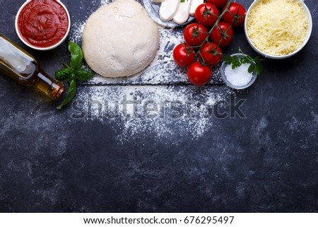 Raw dough for pizza with ingredients and spices on black background.overhead with copy space